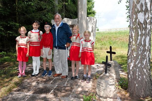 Popis: Antonín Burdych, syn popravených manželů Burdychových, se sokolskými dětmi u pomníku na Končinách v místě, kde byl 30. června 1942 zastřelen německými okupanty jeho otec.