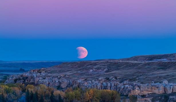 Popis: Pohled na částečné zatmění Měsíce při jeho východu ještě za soumraku. Měsíc se promítá do pásu zemského stínu, nad kterým je narůžovělý Venušin pás. Podobný úkaz můžeme očekávat v pondělí 7. srpna; potemnění Měsíce ovšem bude na pravém spodním okraji.