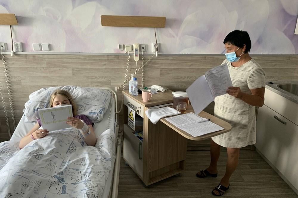Popis: Matrikářka Jiřina Matějová vyřizuje dokumenty s maminkami také přímo na pokoji.
